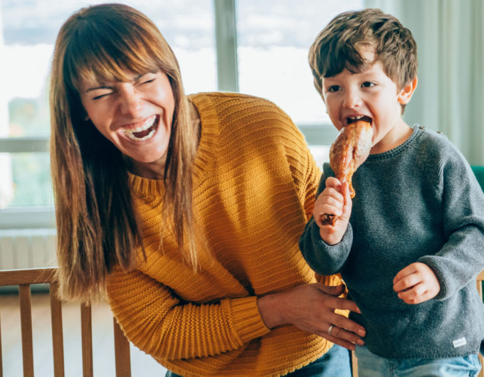 Cute little boy and his beautiful mother having fun during Christmas dinner or lunch.